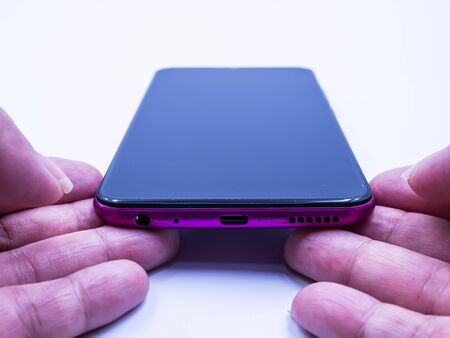 Closeup of smartphone and woman 's hand on gray background. Technology, shopping online, eCommerce, giving, trading, sharing, communication, business and finance concept and idea. Imagens