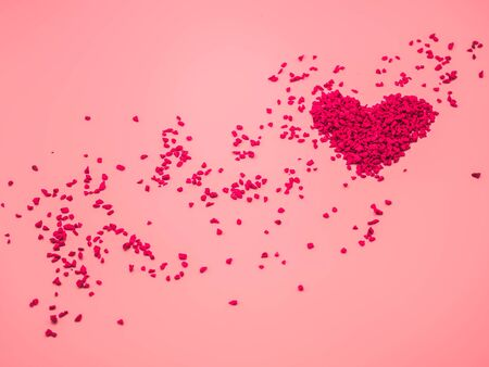Closeup of red heart shape of small gravel on pink pastel color background. Love, valentine, romance, wedding and honeymoon concept and idea.