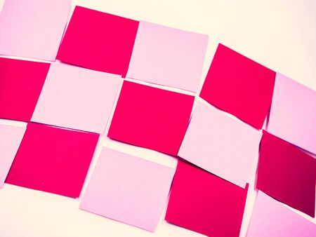 Abstract cross processed tone for vintage and retro background. Closeup of diagonal grids pattern of pink and red note paper texture.