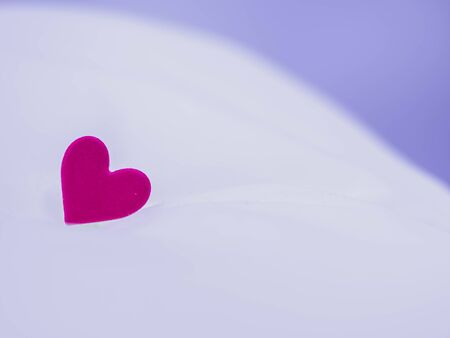 Closeup of vivid and vibrant pink heart shape stickers on white wrinkled sheet bed cover cotton or linen fabric texture and background. Love, valentine, romance, wedding and honeymoon concepts. Imagens