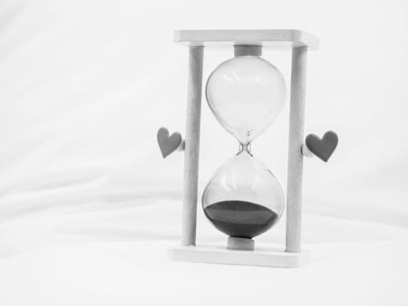 Black and white tone. Closeup of hourglass and heart shape stickers on blurry wrinkled cover sheet bed in the bedroom. Divorce, break up, sadness, loneliness, darkness love and time concept and idea. Stock Photo