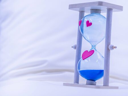 Closeup of hourglass, blue sand, pink heart shape stickers on blurry wrinkled cover sheet bed in the bedroom. Love and time concept and idea. Imagens