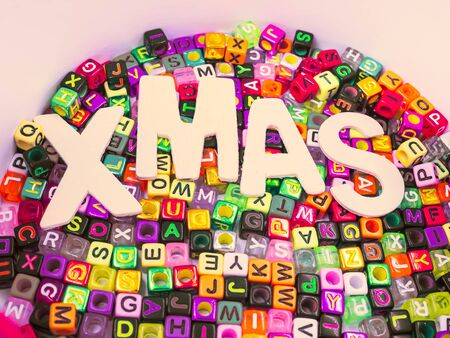 Cross processed tone of wooden alphabet Xmas word on colorful multicolored small plastic alphabet dice background for Merry Christmas anniversary, celebration,party, greeting card concept and idea.