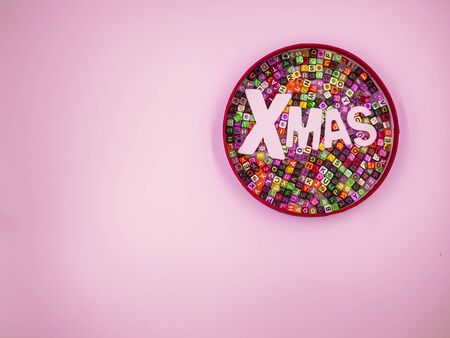 Cross processed of wooden alphabet Xmas word on colorful multicolored small plastic alphabet dice pattern in paper box  on pink pastel background for Merry Christmas anniversary, celebration concepts. Imagens