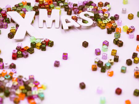 Cross processed tone of wooden alphabet Xmas word with multicolored small plastic dice on gray background  for Merry Christmas anniversary, celebration holidays concept and idea. Imagens