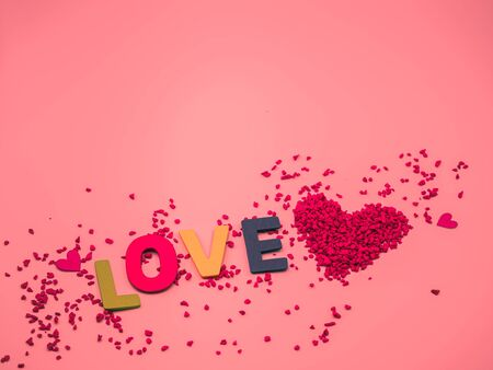 Closeup of red heart shape of small gravel , multicolored colorful wooden alphabet love word on pink pastel color background. Love, valentine, romance, wedding and honeymoon concept and idea. Imagens