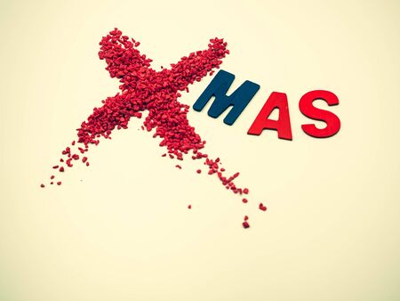 Cross processed tone of Xmas word. Closeup of vivid, vibrant red small gravel with blue, red wooden alphabet on gray gradient background. Merry Christmas anniversary, celebration,greeting card idea.