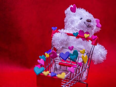 White shaggy dog, red trolley and multicolored heart shape stickers on blurry vivid, vibrant gradient red background and texture. Love, romance, shopping, birthday, party, greeting card concept. Imagens