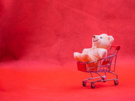 Closeup of cute brown teddy bear doll, sitting in trolley or supermarket cart with soft blurry vivid or vibrant gradient red texture and background for copy space. Business, birthday concept.