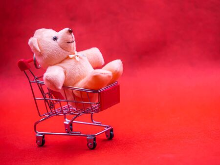 Closeup of cute brown teddy bear doll, sitting in trolley or supermarket cart with soft blurry vivid or vibrant gradient red texture and background for business, birthday concept. Imagens