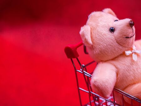 Selective focus at cute brown teddy bear doll 's black eye, sitting in trolley or supermarket cart with soft blurry vivid or vibrant gradient red texture and background for business, birthday concept.
