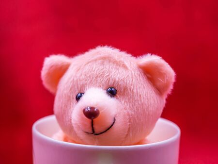 Closeup brown smile teddy bear doll in pink coffee mug on vivid, vibrant gradient red copy space background for happiness,  cheerful emotion, kid, encouragement, strong, positive thinking concepts.