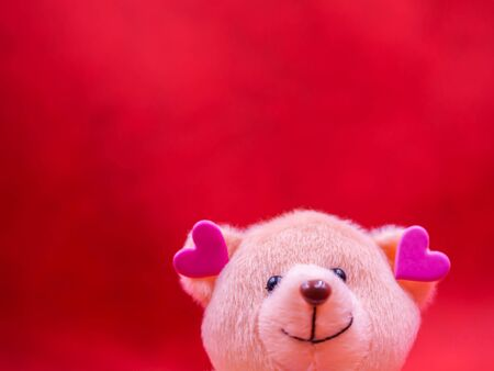 Closeup of smile teddy bear doll with pink heart shape ear on vivid, vibrant red background for happiness, cheerful, love, valentine, positive thinking concepts and ideas. Imagens