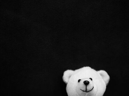 Selective focus at white smile teddy bear doll on darkness black copy space background for contrast, happiness, art creativity, emotion, kid, encouragement, strong, positive thinking concepts. Standard-Bild