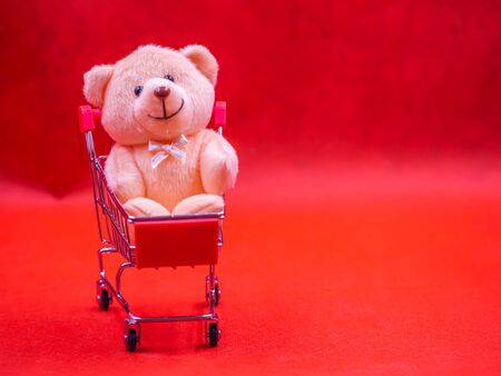 Closeup of cute brown teddy bear doll, sitting in trolley or supermarket cart with soft blurry vivid or vibrant gradient red texture and background for business, birthday concept. Imagens - 138108822