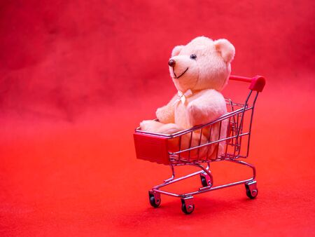 Closeup of cute brown teddy bear doll, sitting in trolley or supermarket cart with soft blurry vivid or vibrant gradient red texture and background for copy space. Business, birthday concept. Imagens - 138108823