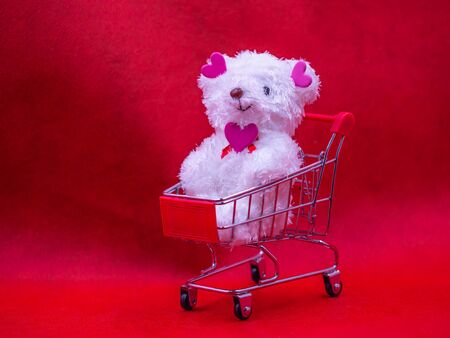 Closeup of white dog doll, pink heart shape stickers and supermarket cart on blurry vivid, vibrant red background for love, valentine, shopping, birthday, business, greeting card concept.