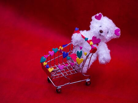 Closeup of white dog doll, multicolored heart shape stickers and supermarket cart on blurry vivid, vibrant red background for love, valentine, shopping, birthday, business, greeting card concept.