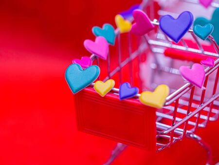Closeup of green heart sticker on  supermarket cart with blurry vivid, vibrant red background for Love, romance, shopping, business, greeting card concept and idea.
