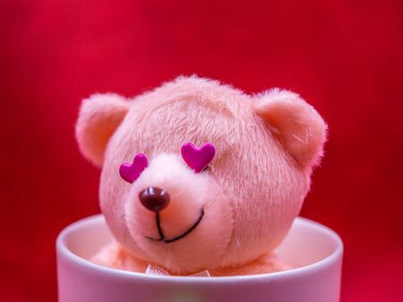 Closeup of smile teddy bear doll with pink heart shape sticker in coffee mug on vivid, vibrant red background for happiness, cheerful, love, valentine, positive thinking concepts and ideas. Imagens