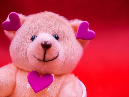 Closeup of smile teddy bear doll with pink heart shape sticker on vivid, vibrant red background for happiness, cheerful, love, valentine, positive thinking concepts and ideas.