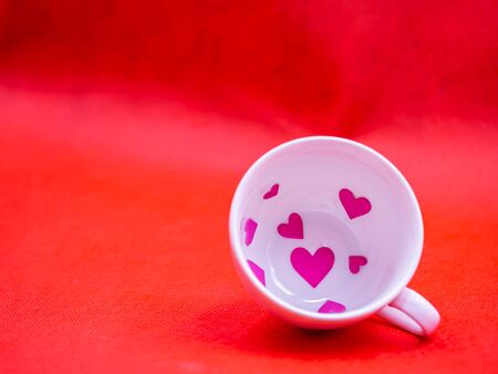Closeup of white coffee cup and pink paper sticker on vivid or vibrant red background for love, valentine, romance, wedding, greeting card concept and idea.