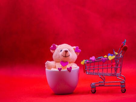 Closeup of smile teddy bear doll with pink heart shape sticker in coffee mug and shopping cart on red background for happiness, cheerful, love, valentine, shopping, business concepts and ideas. Imagens - 138150268