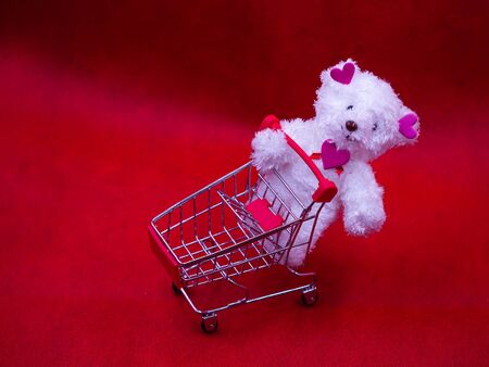 Closeup of white dog doll, pink heart shape stickers and shopping cart on vivid, vibrant red background for love, valentine, shopping, birthday, business, greeting card concept. Imagens - 138150267