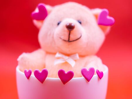 Closeup of pink heart shape sticker with blurry teddy bear doll in white coffee cup on vivid, vibrant red background for happiness, cheerful, love, valentine, positive thinking concepts and ideas.