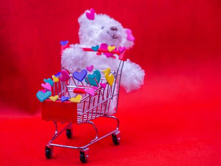 Closeup of heart shape stickers on shopping cart with blurry white dog doll on vivid, vibrant red background for love, valentine, shopping, birthday, business, greeting card concept. Imagens - 138150270