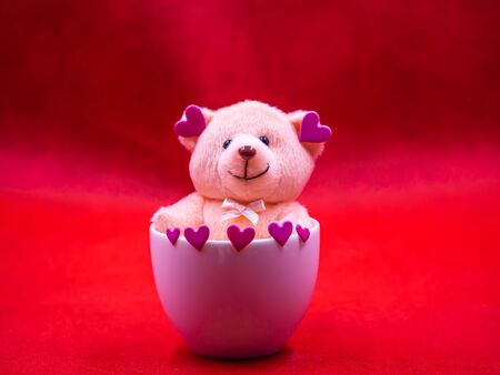 Closeup of smiling teddy bear doll with pink heart shape sticker in white coffee cup on vivid, vibrant red background for happiness, cheerful, love, valentine, positive thinking concepts and ideas.