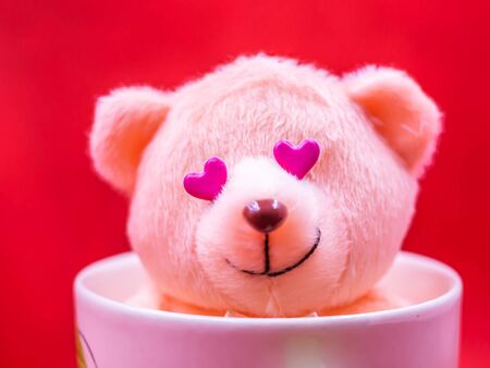 Closeup of pink heart shape sticker,  smiling teddy bear doll in white coffee mug on vivid, vibrant red background for happiness, cheerful, love, valentine, positive thinking concepts and ideas.