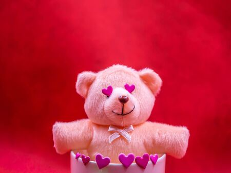 Closeup of pink heart shape sticker and  smiling teddy bear doll in coffee mug on vivid, vibrant red background for happiness, cheerful, love, valentine, positive thinking concepts and ideas.