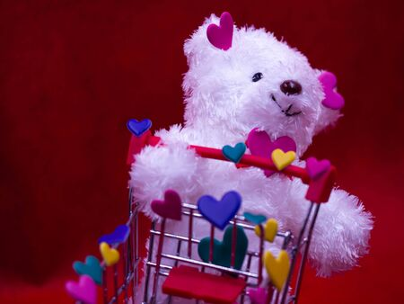 Closeup of white dog doll, multicolored heart shape stickers and supermarket cart on blurry vivid, vibrant red Imagens - 138155360