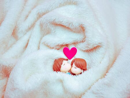 Closeup and vintage tone of sweet and sleeping couple dolls on fabric texture and pink heart sticker for valentines day, love, romance, wedding, relationship, honeymoon, family concept and idea. Imagens - 138898704