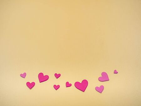 Pink heart shape paper stickers on golden color background for valentines day, love, wedding concept and idea. Imagens