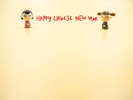 Hand writing of happy chinese new year with chinese couple dolls wear ancient clothing on golden color background. Imagens - 138898707