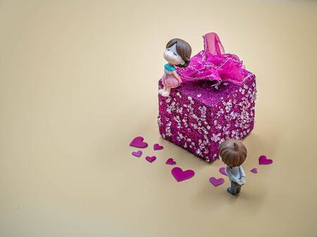 Closeup of cute girl doll sitting on vivid pink gift box on gold colored background and pink heart stickers with boy doll standing for valentines day, love, reconcile, relationship concept and idea. Imagens - 139074943