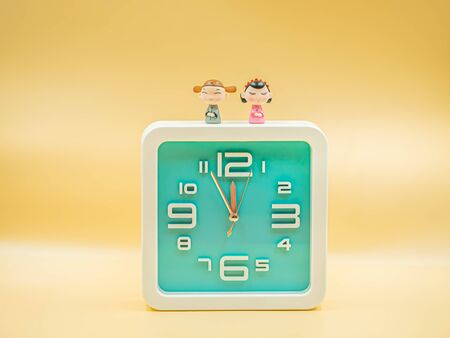 Square shape clock with cute chinese dolls wear ancient clothing on gold colored gradient background for waiting or countdown time to chinese new year day concept. Imagens