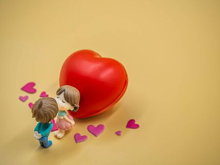 Closeup of couple kissing cute dolls on gold colored background with pink heart stickers and vivid red foam heart for valentines day, love and relationship concept and idea. Imagens - 139074944