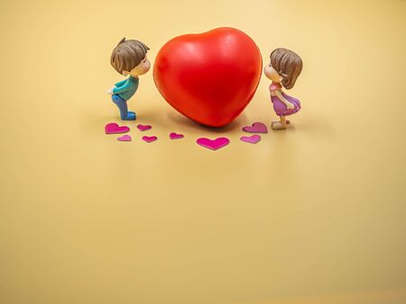 Closeup of couple kissing cute dolls on gold colored background with pink heart stickers and vivid red foam heart for valentines day, love and relationship concept and idea.