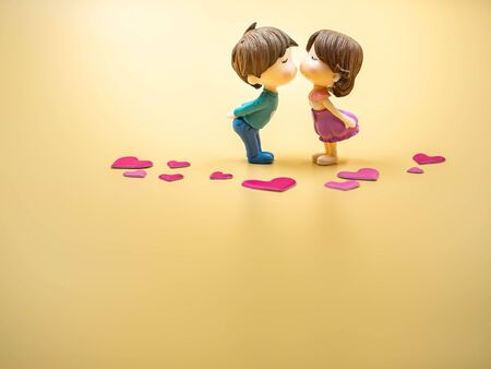 Closeup of couple kissing cute dolls on gold colored background with pink heart stickers for valentines day, love and relationship concept and idea.