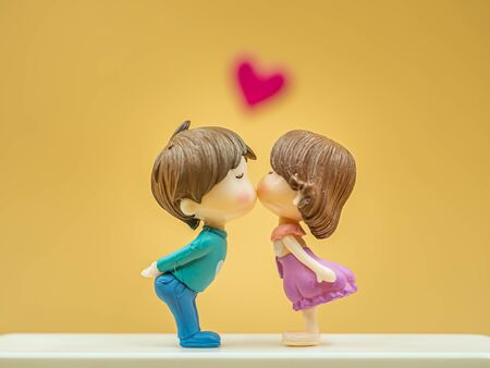 Closeup of couple kissing cute dolls on white plastic floor with blurry gold colored and pink heart sticker for valentines day, love and relationship concept and idea.