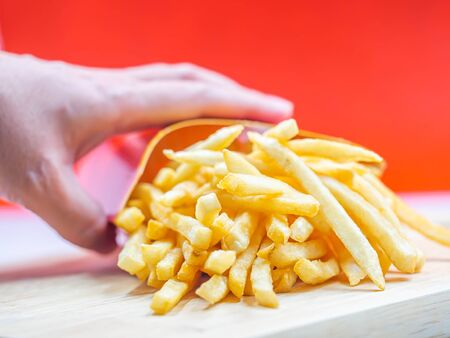Closeup of french fried on wooden plate and woman 's hand with blurry red background.