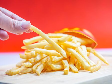 Closeup of french fried on wooden plate and woman 's hand with blurry red background. Imagens - 141282805