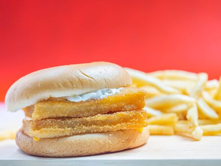 Closeup of fish burger with blurry french fried and red background. Imagens - 141282803