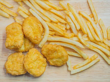 Top view or directly above of closeup crispy nuggets and french fried on wooden table.