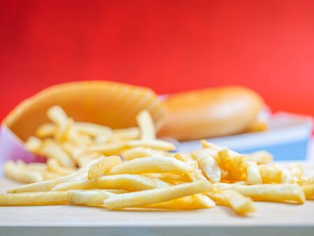 Closeup of crispy french fried with blury fish burger and red background. Imagens - 141282812