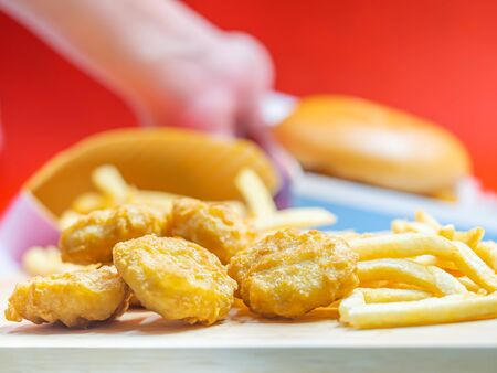 Closeup of crispy nuggets with blurry woman 's hand, fish burger and red background.