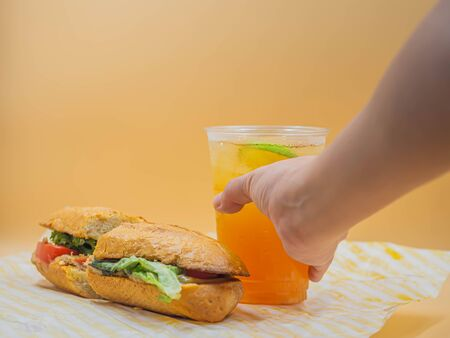 Bad serving food of poor quality tuna sandwich with not fresh vegetable, ice lemon tea with woman 's hand and gradient yellow background. Imagens